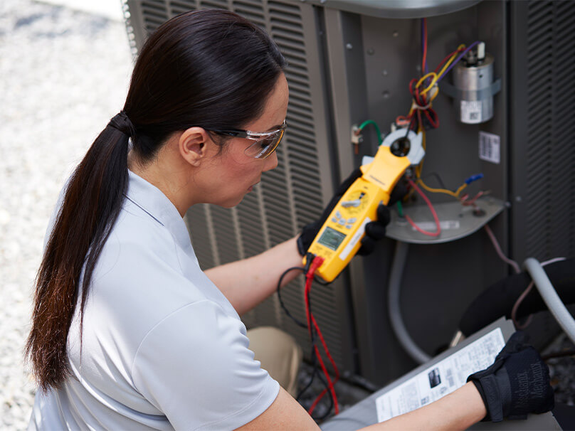 Woman working on an air conditioning unit